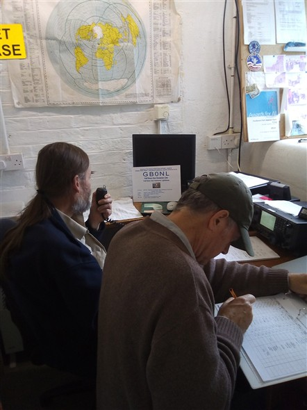 Photo:GB0NL on the air, with the operator on the mike and the call logger recording the details.