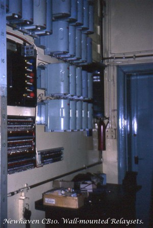 Photo:Wall-mounted relaysets in the Apparatus Room of Newhaven Manual Telephone Exchange. One was required for every outgoing junction to Brighton, Eastbourne, Lewes, Peacehaven and Seaford. There were many more out-of-picture. Nearer the camera is an alarm panel with different coloured bulbs, and beneath that, several rows of 'alarm-reporting' fuses that would cause a lamp on the alarm panel above to indicate the location of a blown fuse.