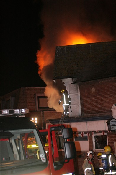Photo:Fire fighter on the roof by the upstairs bar